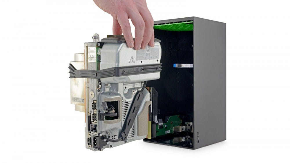 The innards of an Xbox Series X, held in place by black rubber straps.