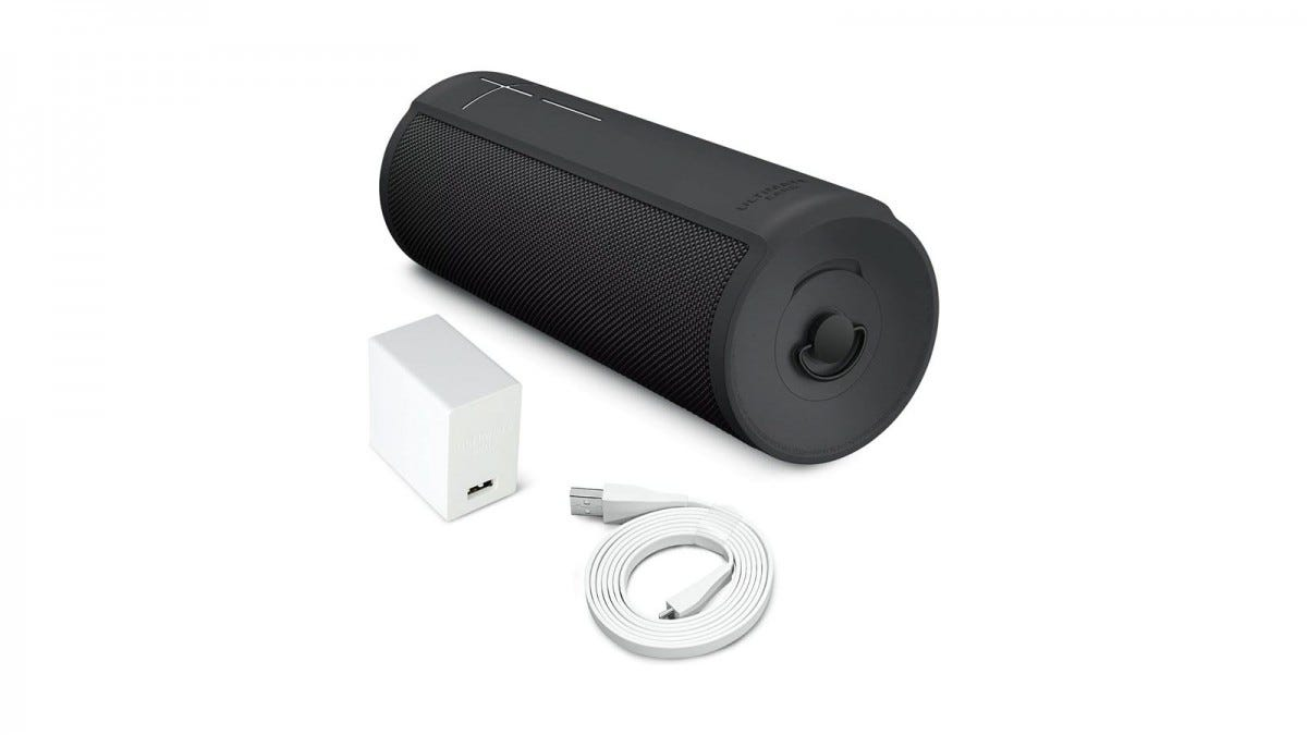 The Ultimate Ears Megablast speaker with charging cord and block.