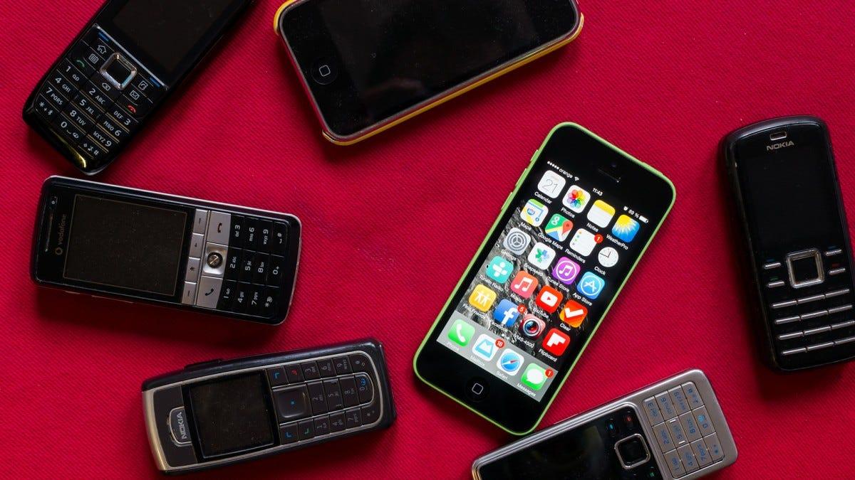 An working iPhone surrounded by broken Nokia flip phones.