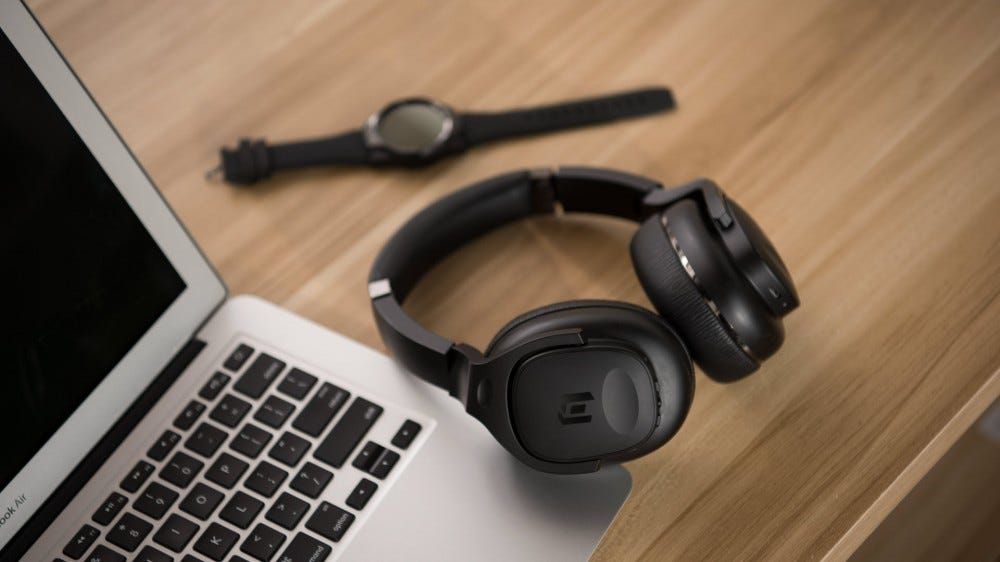 A set of TicKasa headphones next to a Macbook Air.