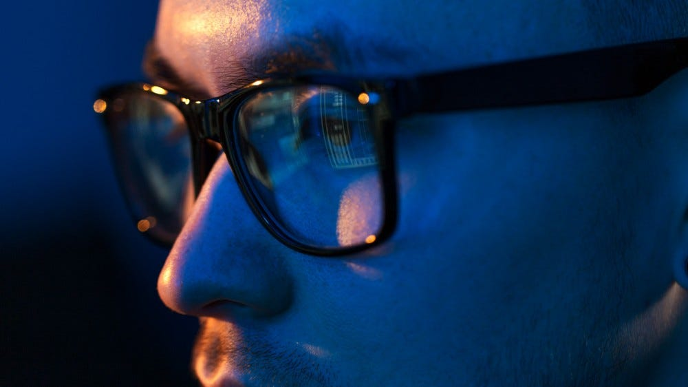 Close up of a person wearing eyeglasses looking at a computer screen in darkness