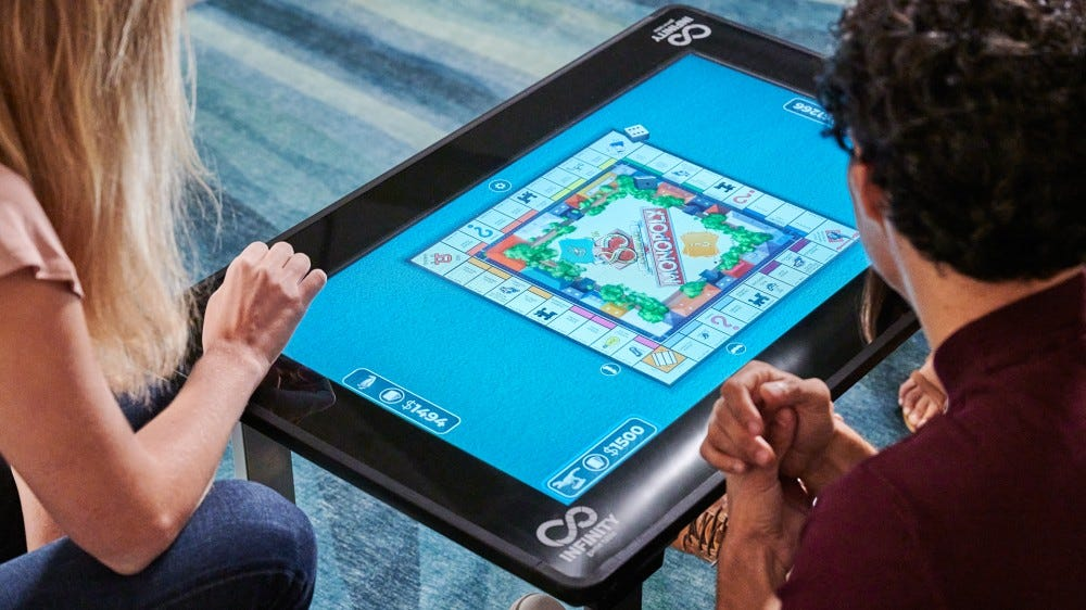 Two people playing on an electronic board game table.