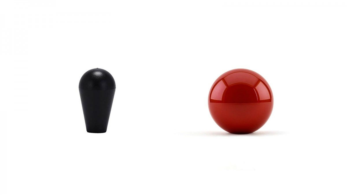 A black bat-shaped joystick top on the left, and a red ball joystick top on the right.