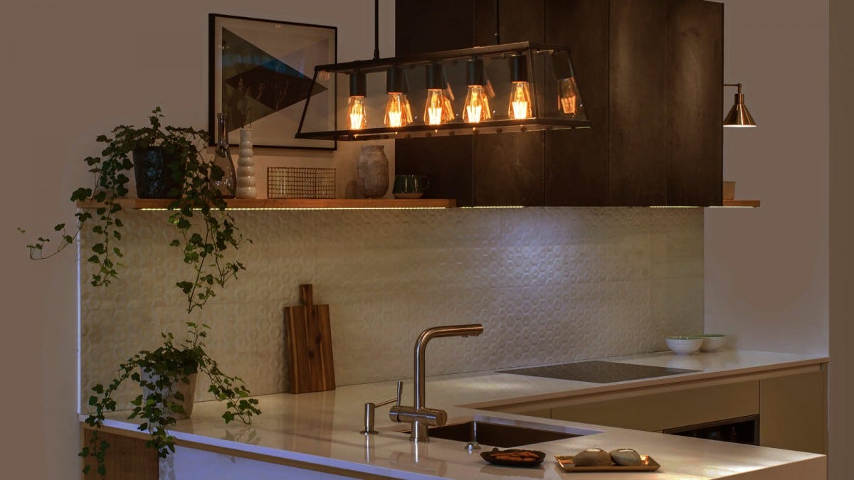 A kitchen with several yellow tinted smart light bulbs.