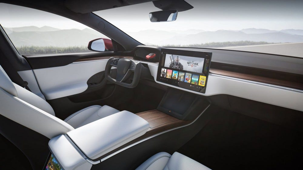 The interior of a Tesla Model S, with 'The Witcher 3' playing on the infotainment system.