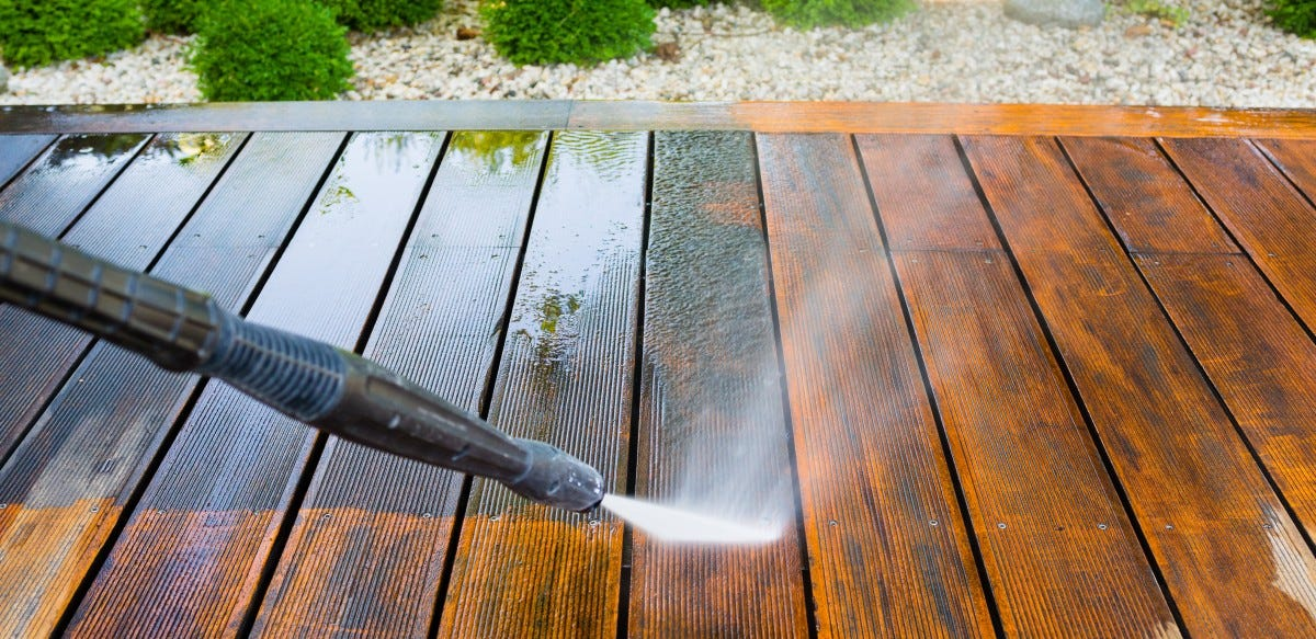 A pressure washer cleaning a deck.