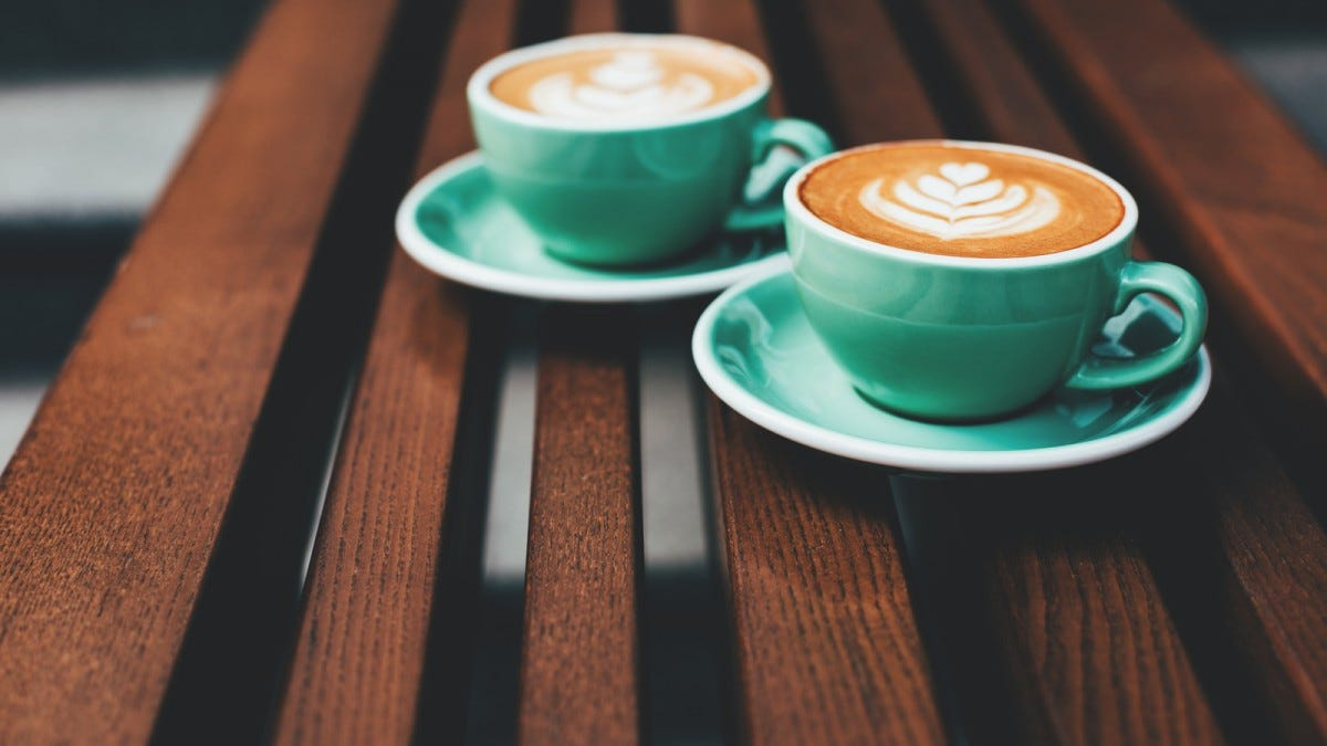 Two cups of cappuccino with latte art on wooden background.