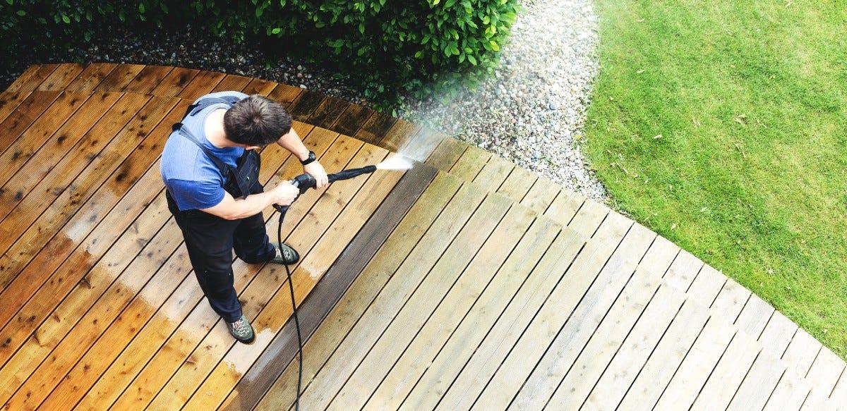 A man pressure washing his deck.
