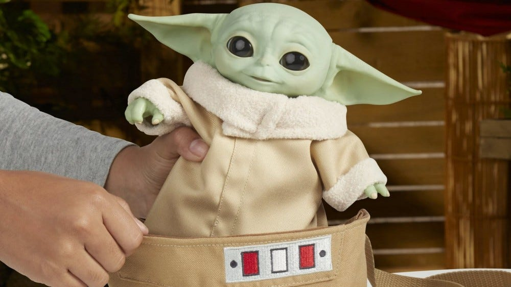 An Animatronic Baby Yoda in a cloth carrying bag.
