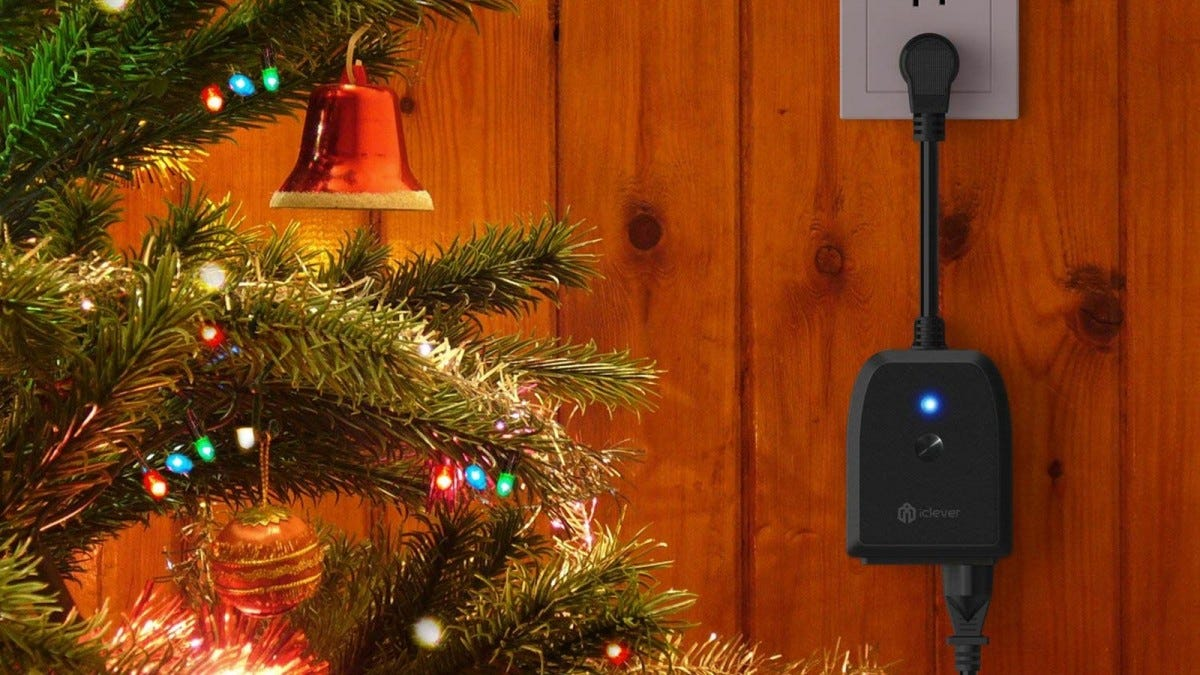 An iClever smart plug plugged into the wall beside a lit up Christmas tree.