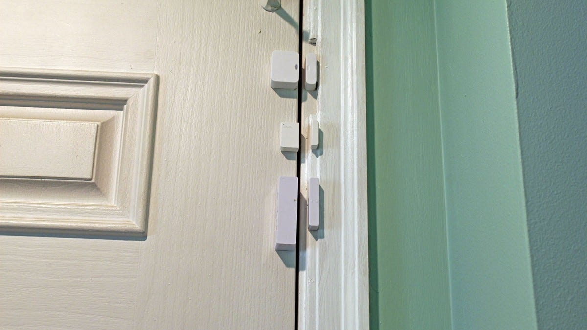 A Simplisafe, Wyze, and Lockly contact sensors lined up vertically on a door.