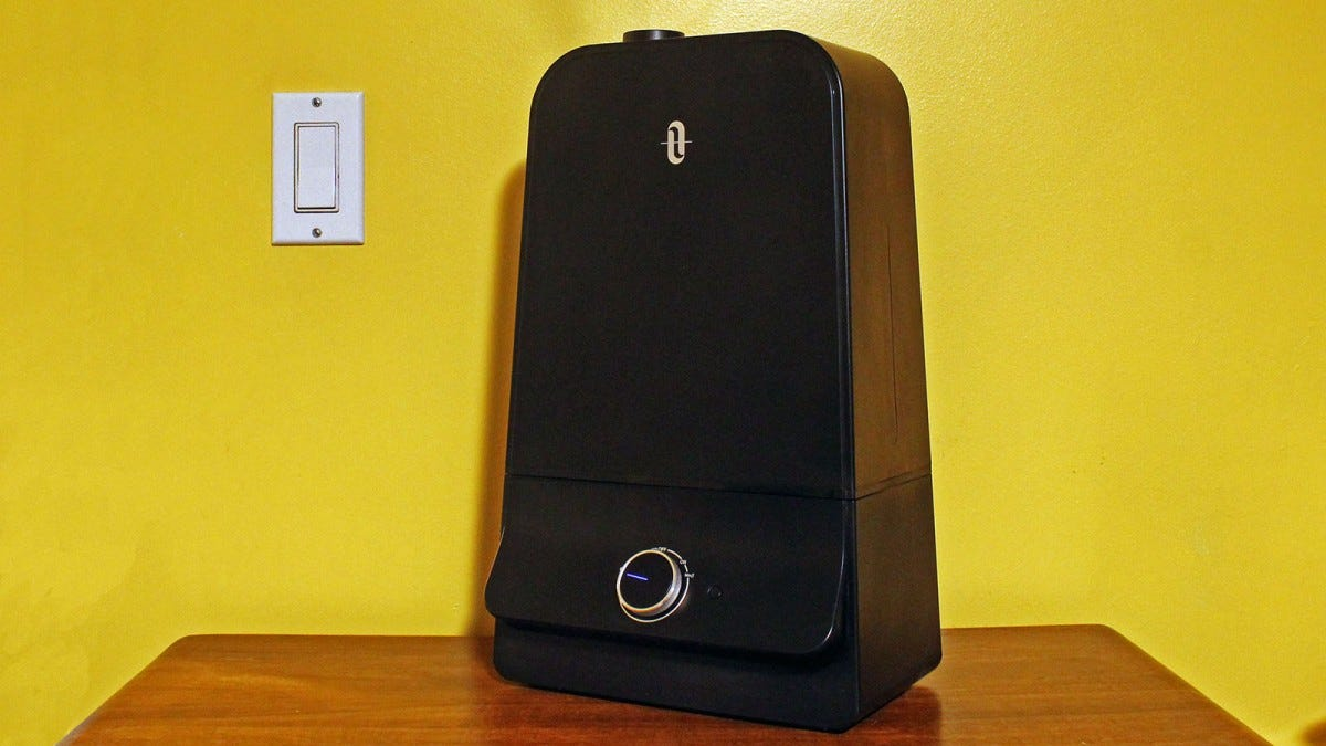 The Taotronics humidifier in front of a yellow wall.