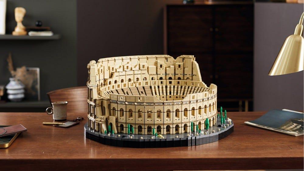 A LEGO Roman Colosseum on a desk, near a much smaller coffee mug.