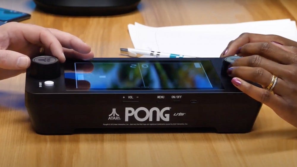 A portable 'Pong' machine on a coffee table.