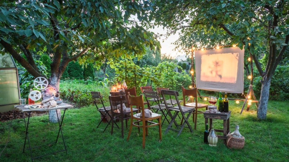 Summer outdoor cinema with retro projector in the evening and chairs and decor