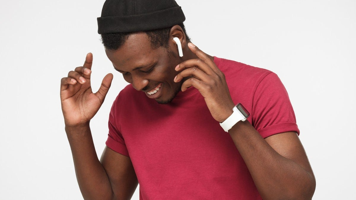 A man smiling while listening to music on his wireless earbuds.