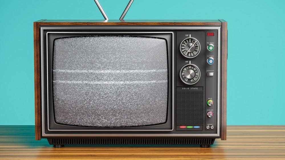 A photo of an old tube TV with bunny ears.