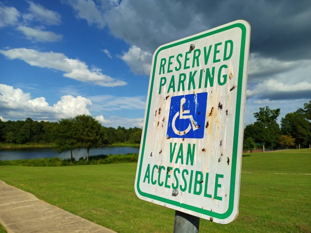 A parking sign with dark clouds, green grass, and blue sky in the background