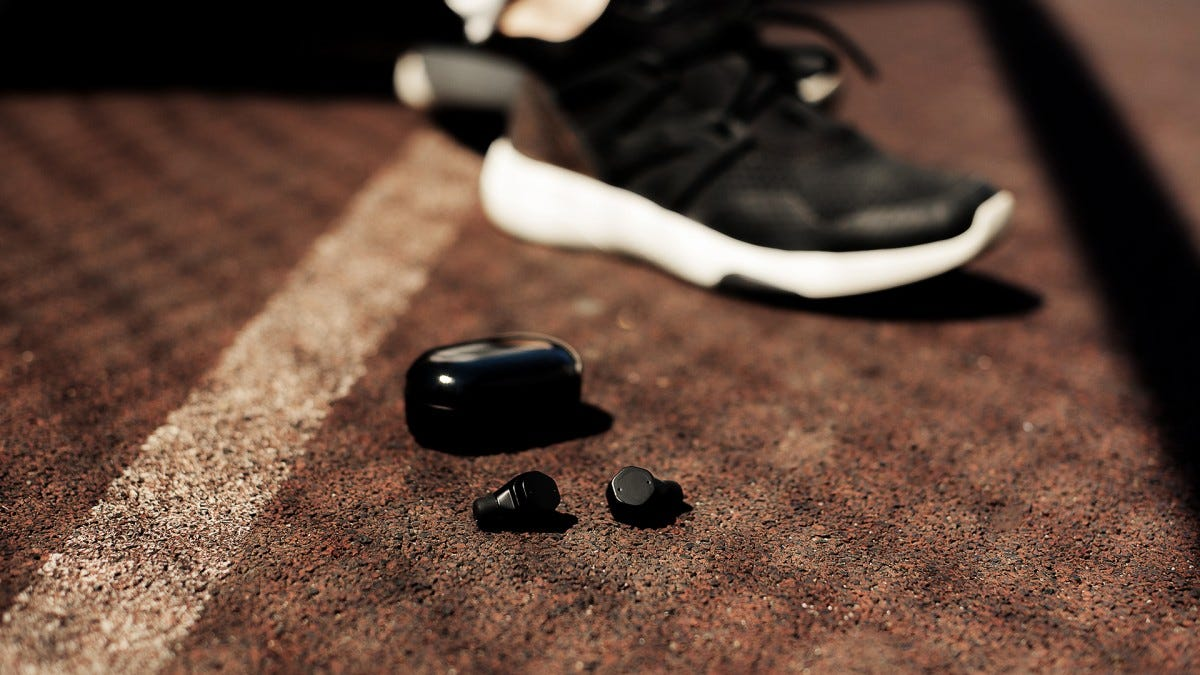 A man's foot in a sneaker on a concrete athletic court next to a pair of wireless earbuds and their case.