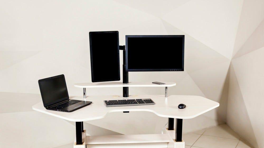 Több monitor beállítása fehér, szögletes asztalon