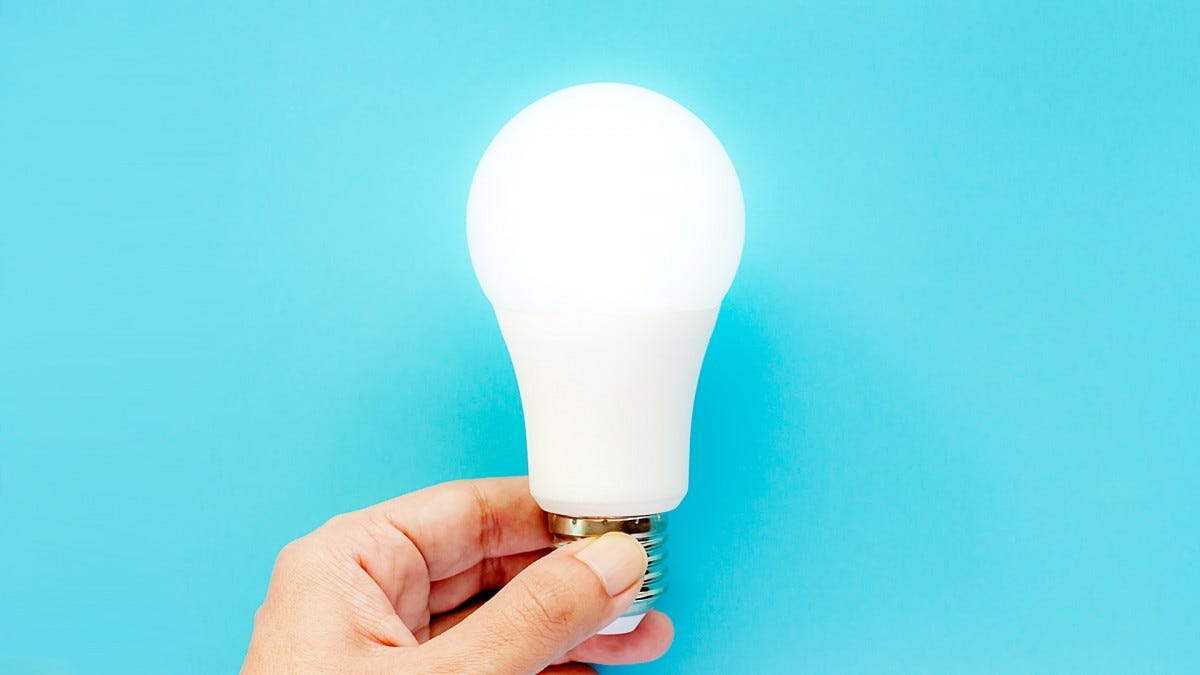 A hand holding a smart bulb.