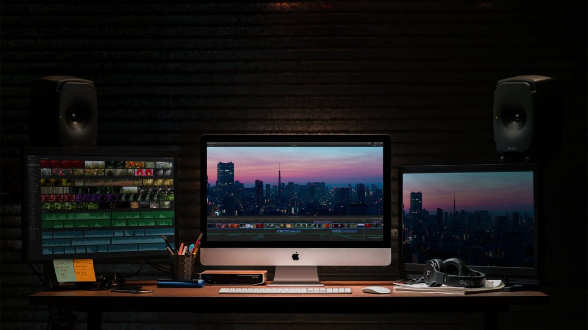 an iMac with two external monitors editing video
