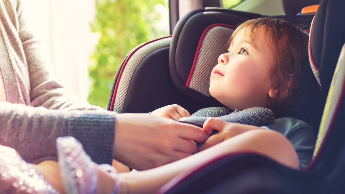 Toddler being buckled into a rear-facing car seat.
