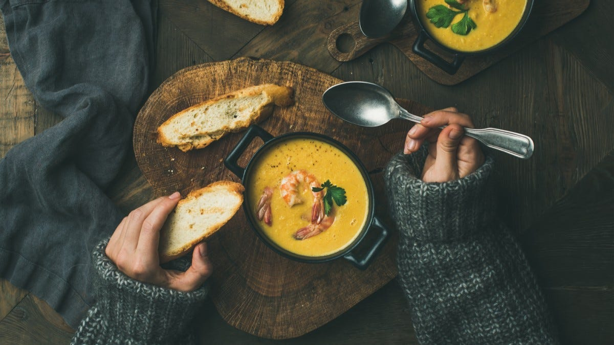 Hands holding a piece of a bread and spoon over a bowl of corn chowder with prawns.
