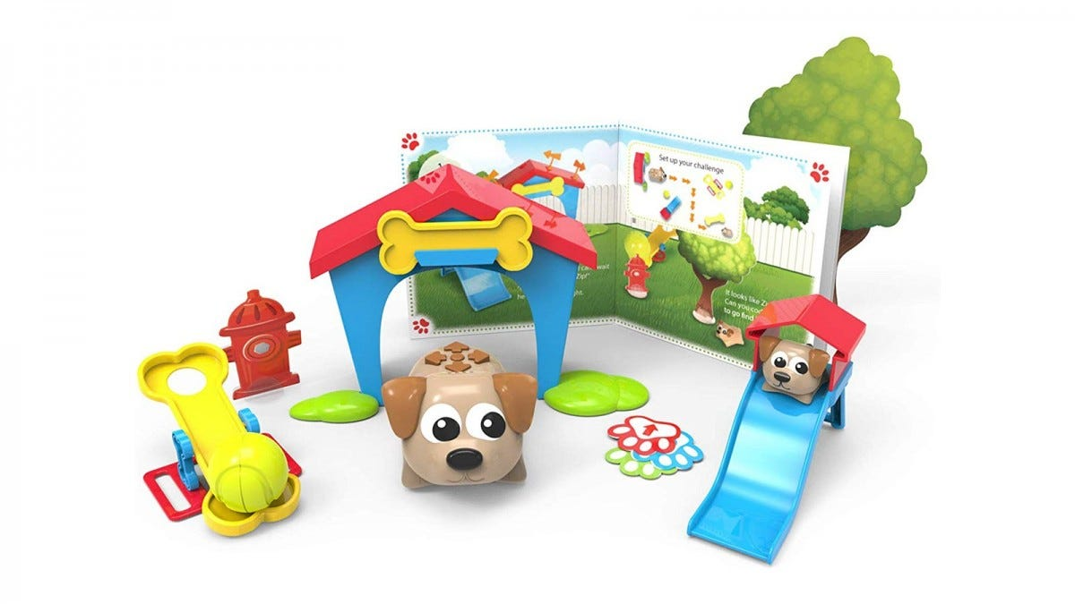 A coding critters toy, featuring two pups, a slide, a dog house, and a book.