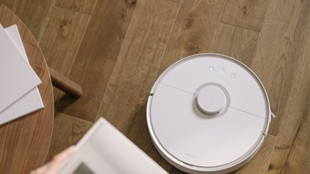 A white Roborock S4 vacuum cleaner moving through a living room.