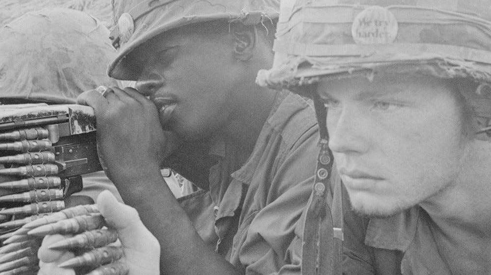 Two American soldiers operating a machine gun.