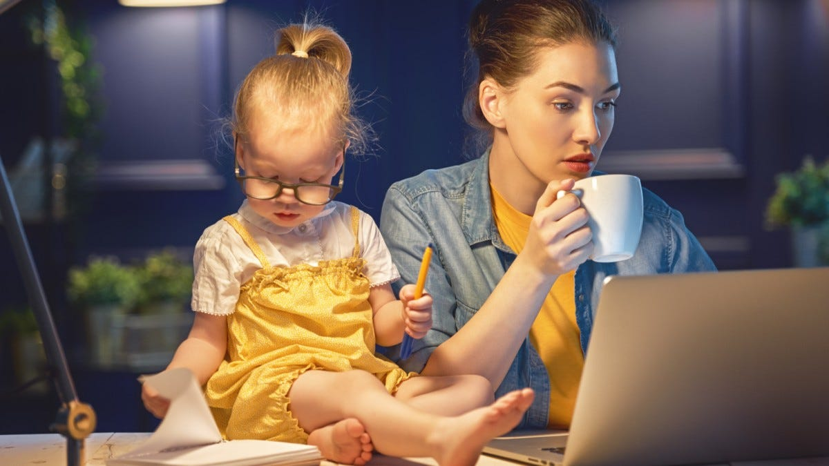 A woman with a laptop and coffee trying to get work done with a toddler sitting beside her