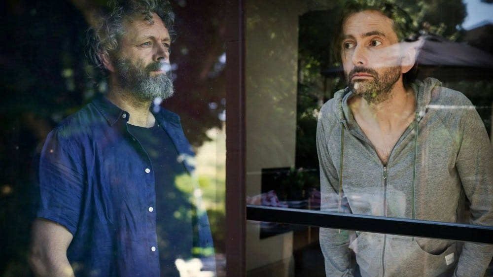 Michael Sheen and David Tennant looking through a glass window.