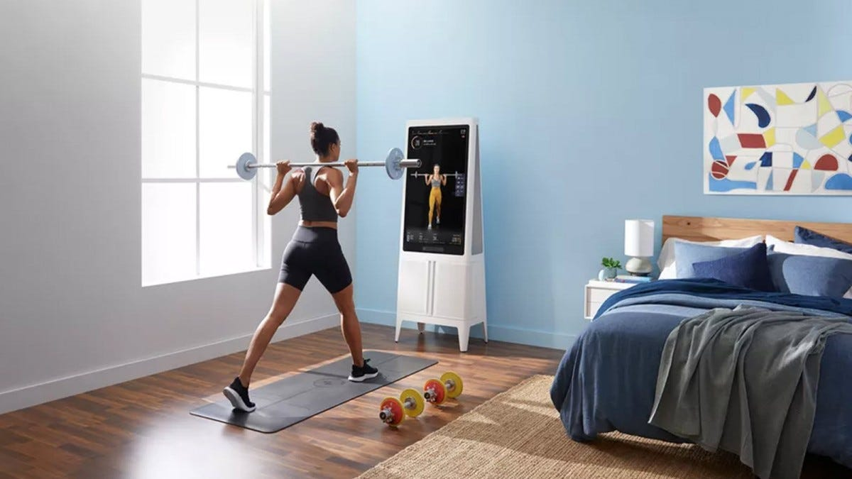 A woman lifting a barbell in front of the Tempo Studio