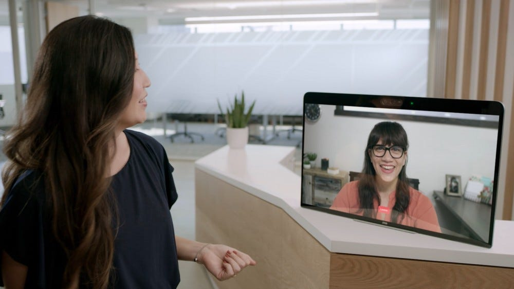 A virtual receptionist greets a guest from a Zoom Rooms for Touch device.