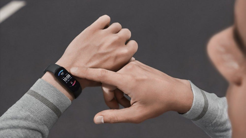 A man looking down at a fitness band.
