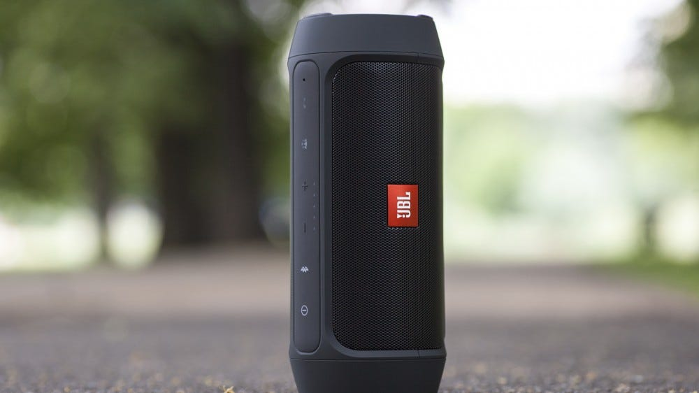 A photo of the JBL Charge 2 smart speaker on some concrete.