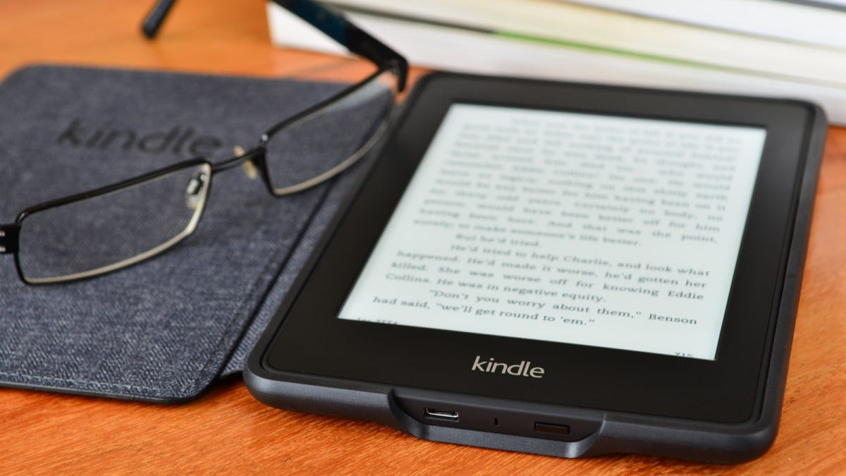 A pair of glasses resting on a Kindle e-reader.