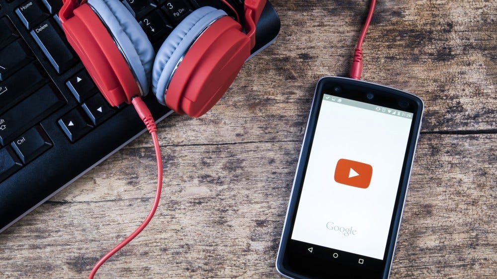Smartphone with loading YouTube Music app on screen lying on desk with headphones