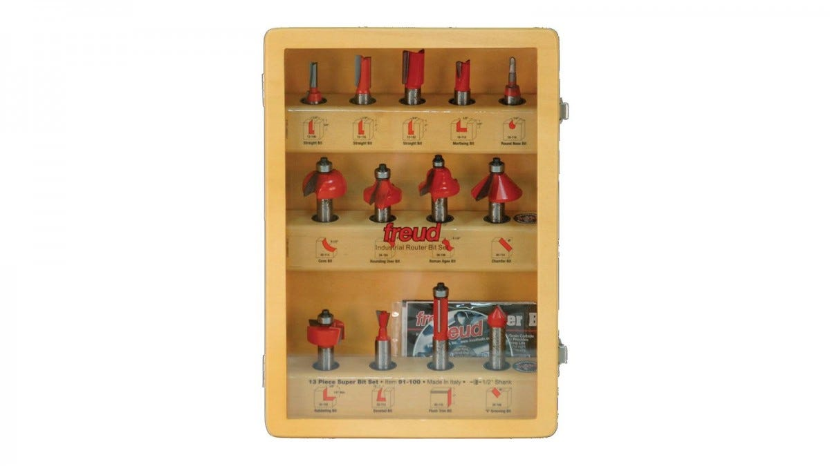 A set of 12 red router bits in a box with a glass front.