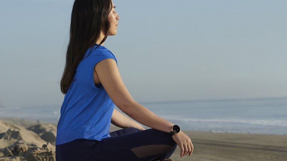 Woman meditating on a beach wearing a Wear OS by Google smartwatch