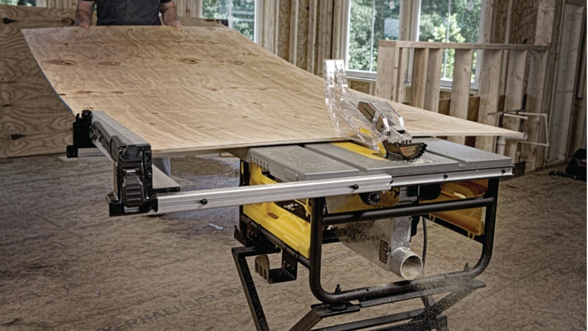 A man feeding a large plywood piece to a DeWalt table saw.