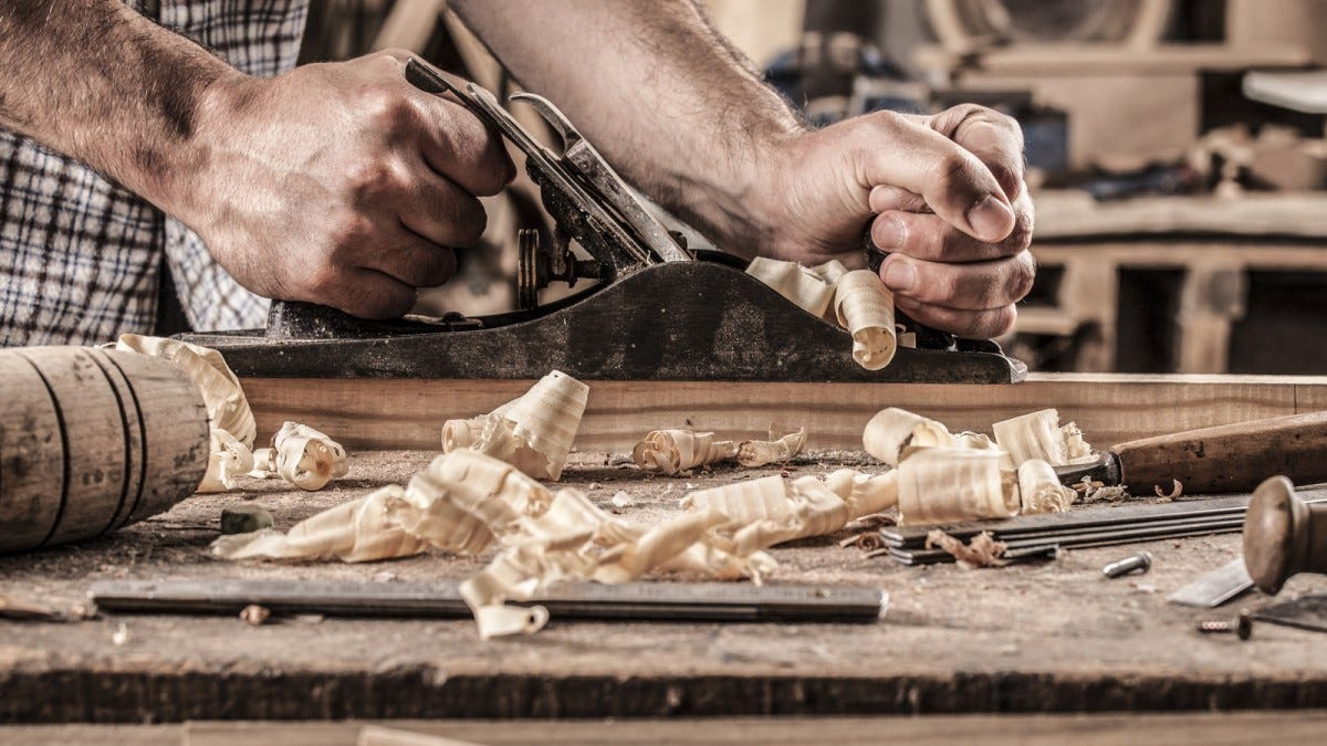 A man planing a piece of oak on a workbench.