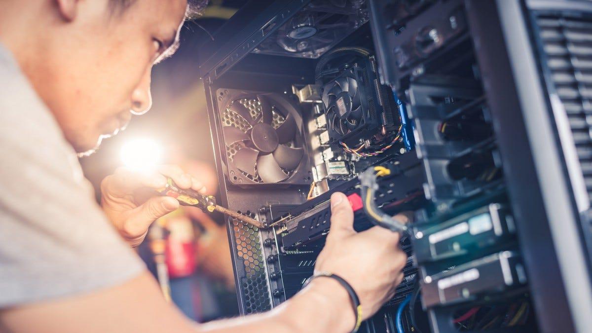 Một người đàn ông xây dựng một máy tính để bàn.