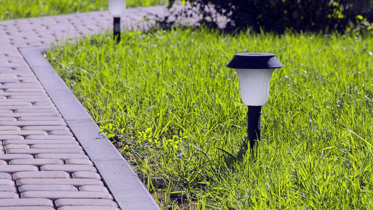 Two path lights along a brick walkway.