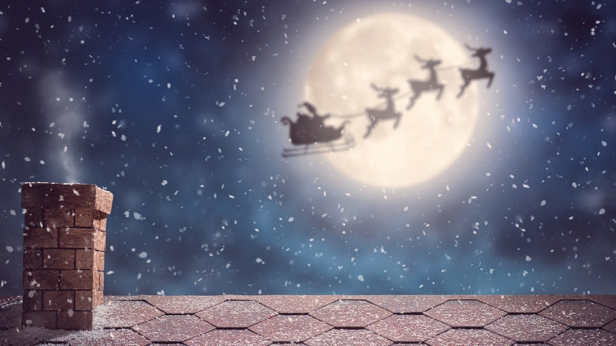 Santa flying over the roof of a house