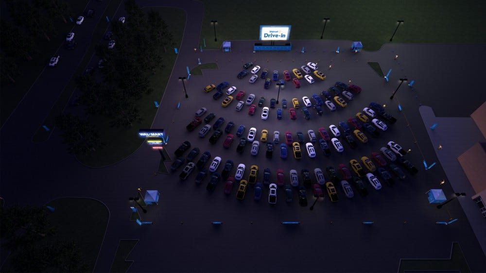 Walmart Drive-in experience cars parked in a parking lot watching a movie