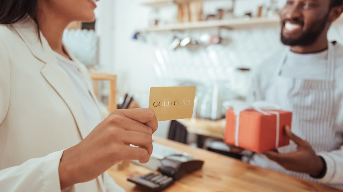 A woman holding a Gold Card to pay for a wrapped gift a man behind a counter is handing her.