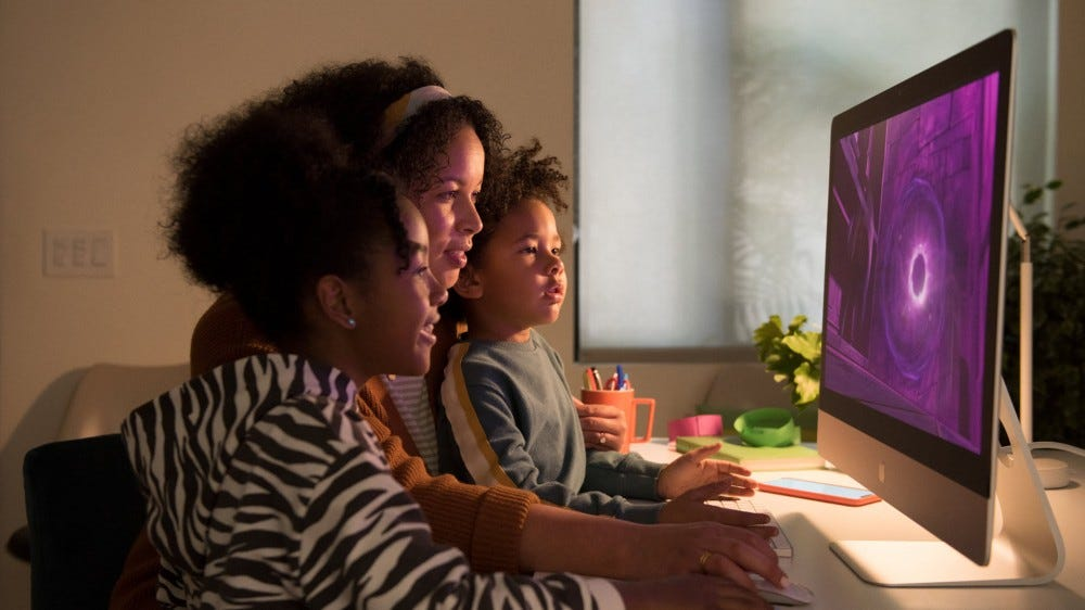 A family looking at the new iMac 27-inch.