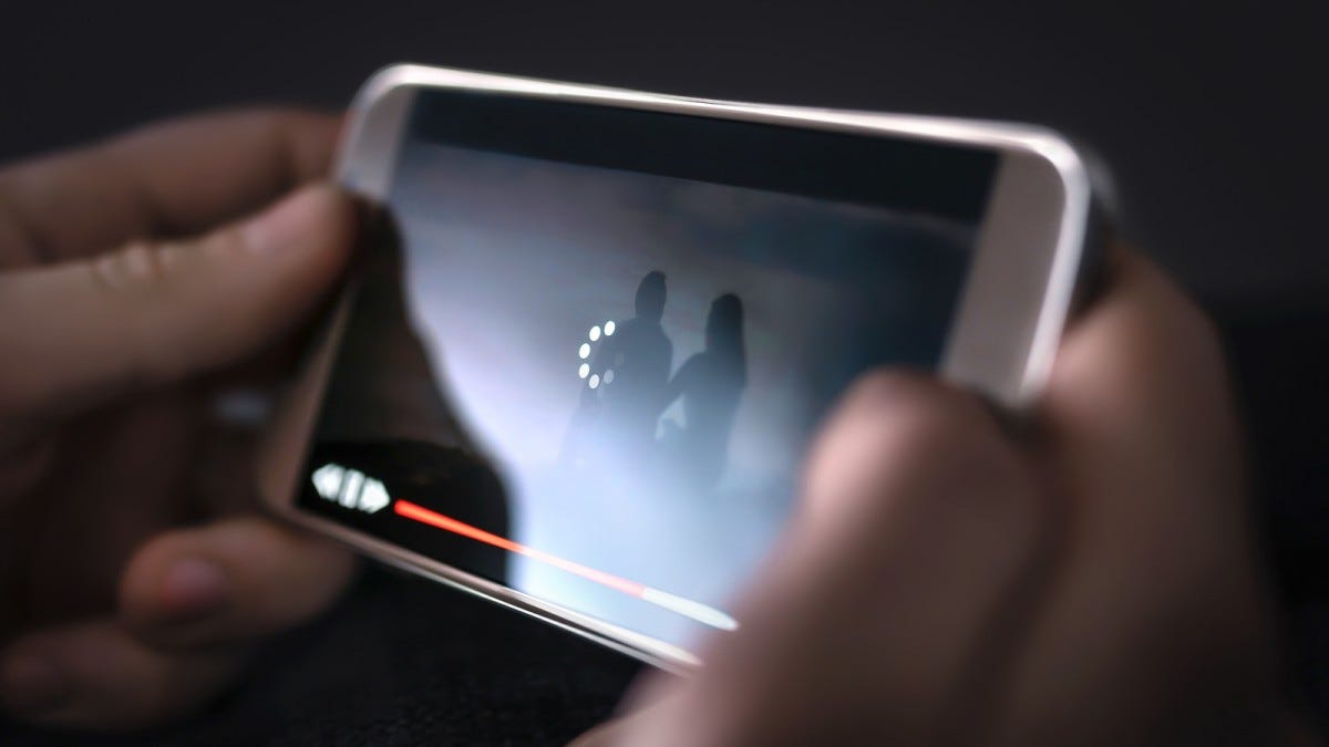 A person holding a phone, with a loading icon over a streaming video.